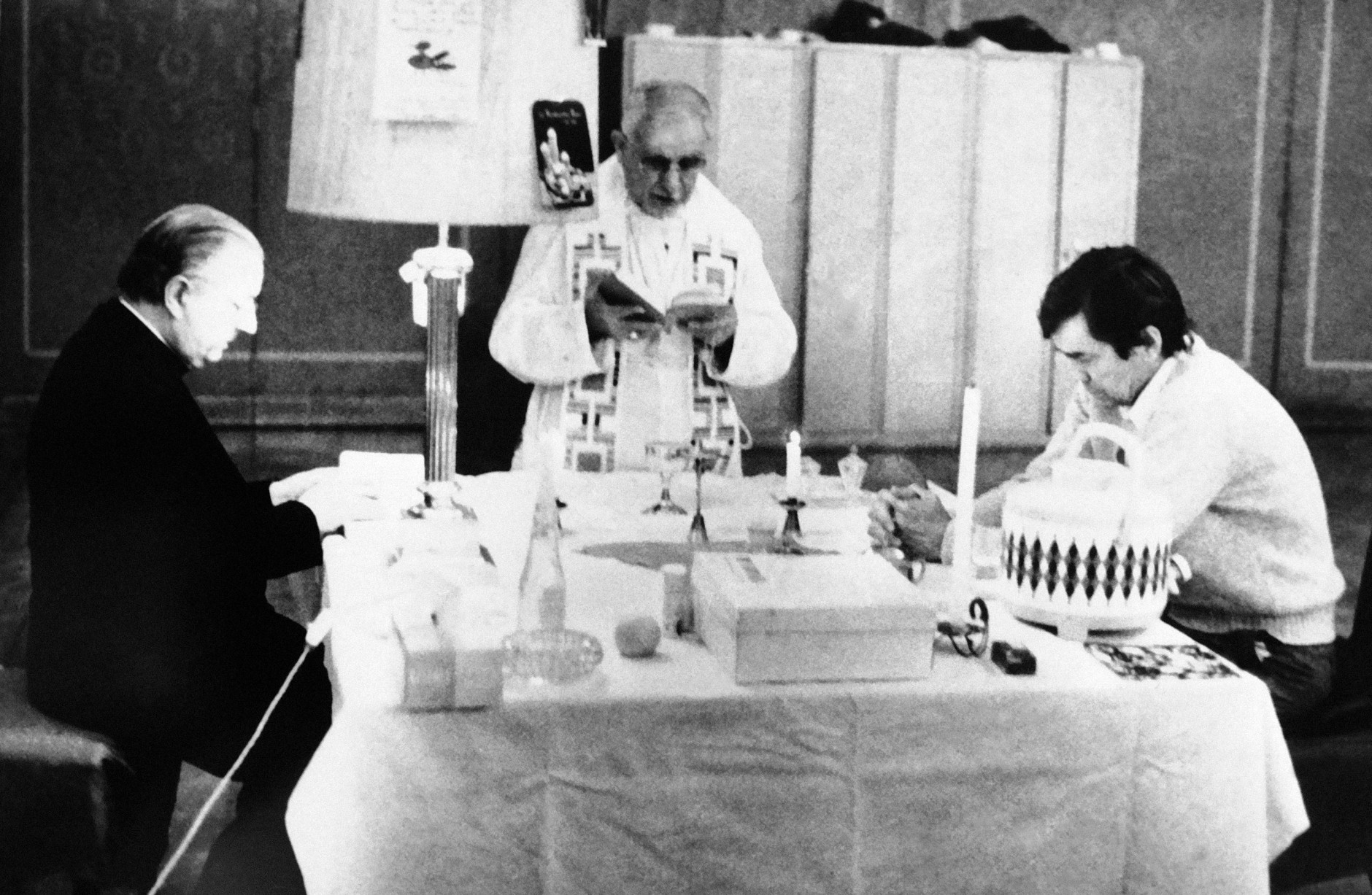 Bruce Laingen, right, U.S. charge d'affairs in Iran, sits with Vatican envoy Anibale Bugnini as Iranian Roman Catholic archbishop of Tehran Youhannan Semaan Issayi, center, celebrates Christmas service at Iran's Foreign Ministry in Tehran on Friday, Dec. 26, 1980. (AP Photo)