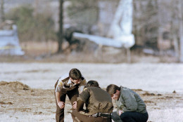 Airplane part in background marks the area where Ricky Nelson's private plane crashed on New Years Eve, in De Kalb, northeast of Dallas, Texas. Seven of the nine occupants, including Nelson, were killed in the crash. Unidentified investigators look over the crash site, Jan. 1, 1986.  (AP Photo/Carlos Osorio)