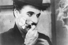 """** FILE ** Charlie Chaplin holds a rose in this photo from the final scene in his 1931 silent film """"City Lights"""".   The film is among the American Film Institute's best romantic comedy movies. (AP Photo)"""