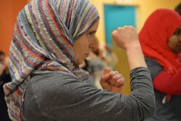 Franzen holds up her fists as she prepares to try her front kick. (WTOP/Omama Altaleb)