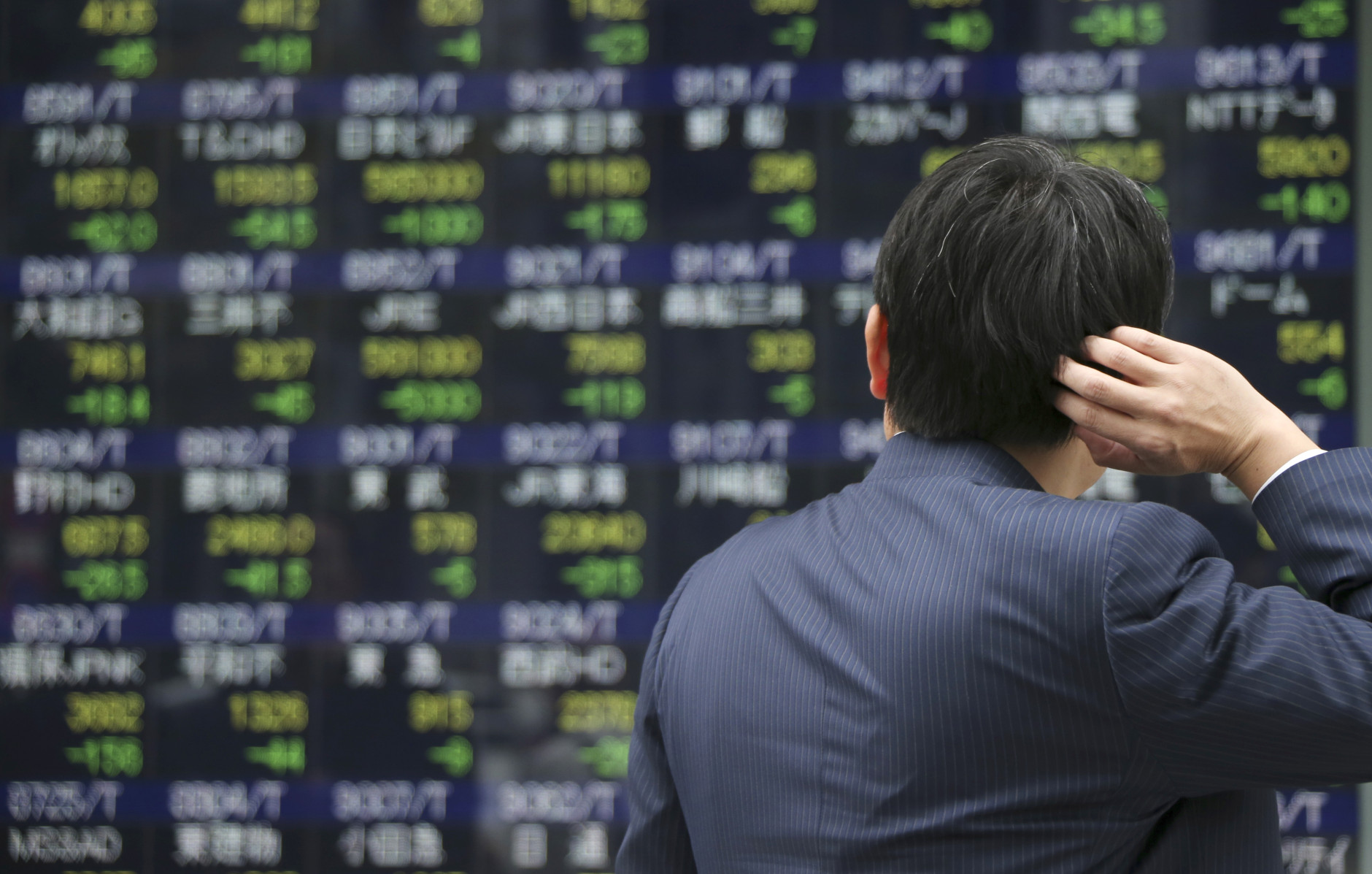 A man looks at an electronic stock board of a securities firm in Tokyo, Monday, Dec. 14, 2015. Asian stock markets were mostly lower Monday following Wall Street's losses as investors awaited the U.S. Federal Reserve's decision this week on whether to go ahead with an interest rate hike. (AP Photo/Koji Sasahara)