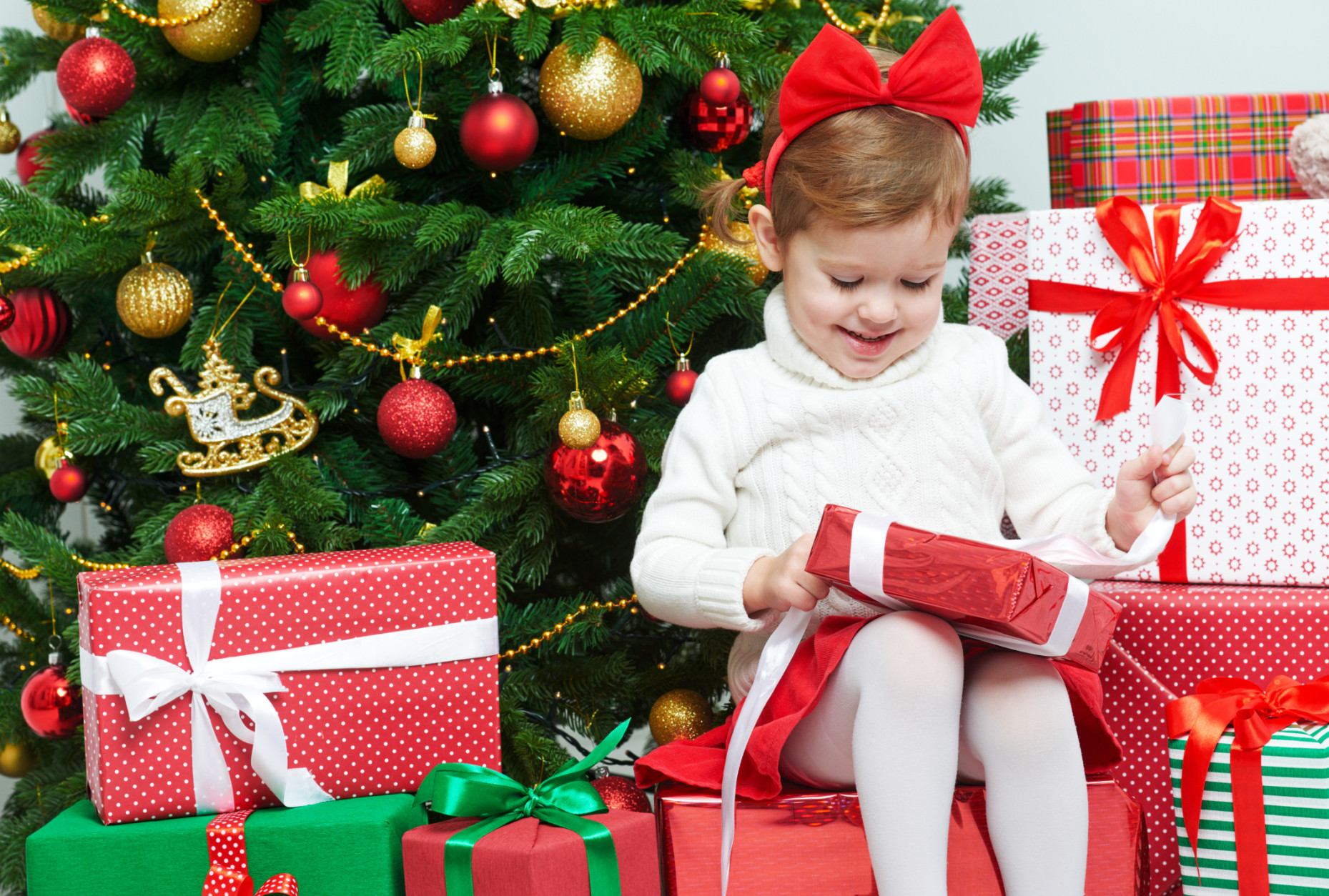 happy child opens Christmas gifts near  tree