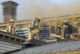 Firefighters open up the roof while working on a fire at the Annapolis Yacht Club in Annapolis, Md., on Saturday, Dec. 12, 2015. (Matthew Cole/Capital Gazette via AP) MANDATORY CREDIT
