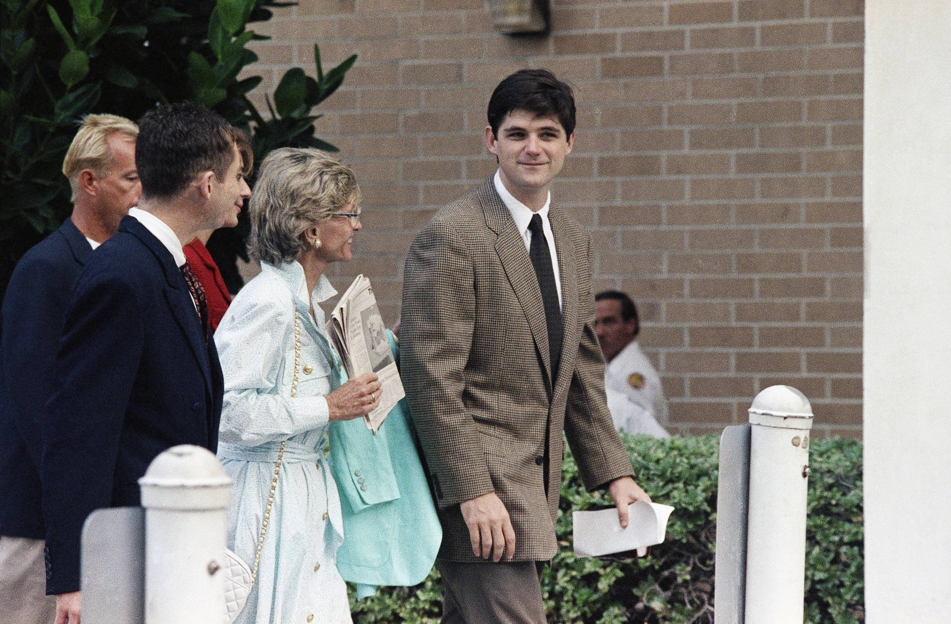William Kennedy Smith, right, enters the Palm Beach County Courthouse in West Palm Beach, Dec. 2, 1991 with members of his family for the first day of his sexual assault trial. His mother Jean is in the center holding a newspaper. (AP Photo/Chris O'Meara)