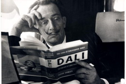 UNITED KINGDOM - NOVEMBER 21:  Salvador Dali reading his biography, 6 May, 1959. A photograph of the Spanish artist Salvador Dali (1904-1989), taken by Terry Fincher for the Daily Herald newspaper. Dali is reading Fleur Cowles' book 'The Case of Salvador Dali' (1959), whilst on a train from Folkestone, having travelled from France. Cowles' book was an authorised biography of Dali. With a studied expression of shock on his face, Dali enjoys the photo opportunity. One of the most famous, charismatic and notorious artists of the twentieth century, Dali devoted himself to drawing and painting from an early age. Hugely influential as a Surrealist, one of his most famous paintings is 'The Persistence of Memory'. By the 1950s Dali had turned to demonstrating scientific, historical and religious themes in his work. In later life he founded both the Dali Theatre-Museum, Figueres, Spain and the Gala-Salvador Dali Foundation, Pubol Castle, Spain - the latter to manage his legacy.  (Photo by Daily Herald Archive/SSPL/Getty Images)