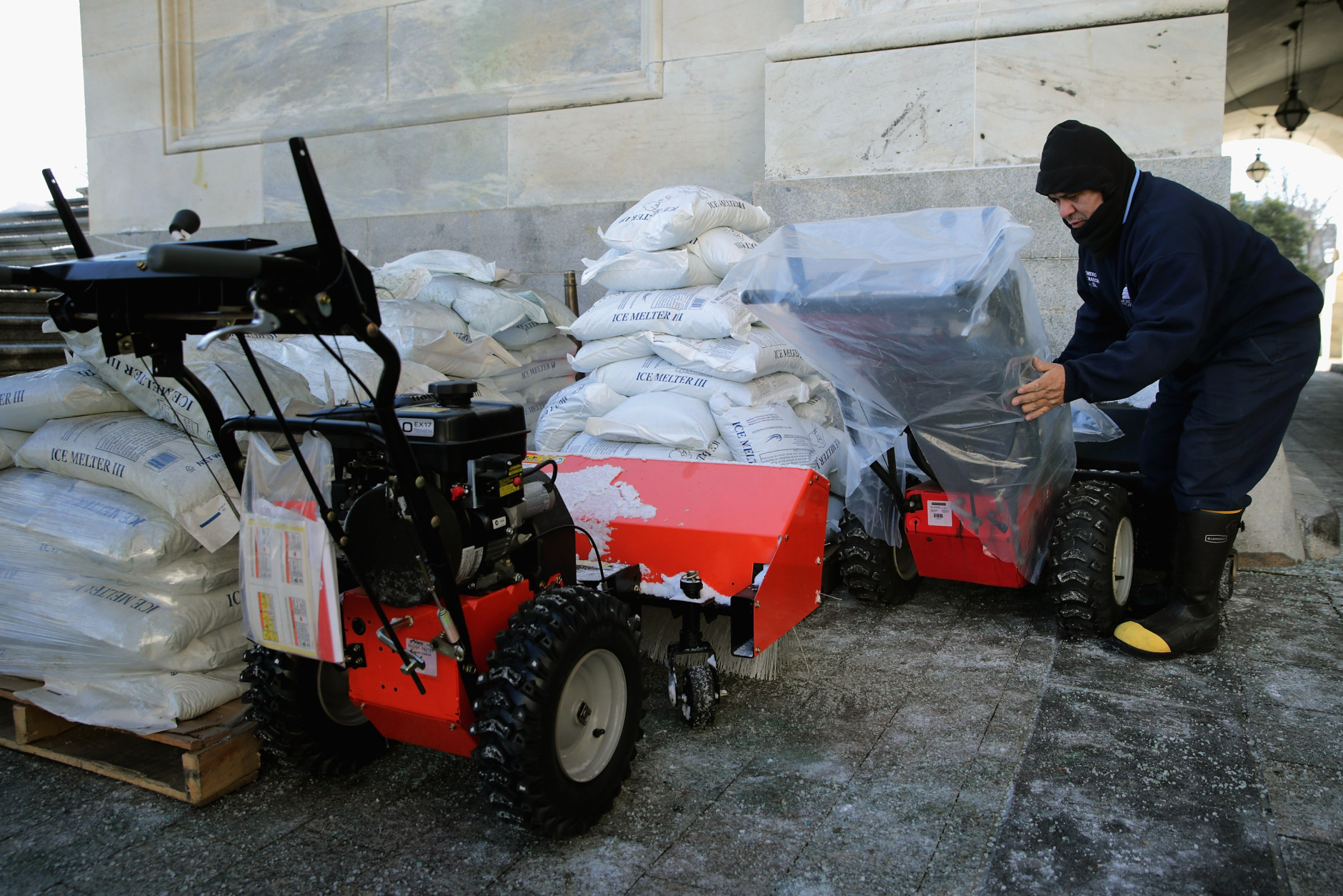 Stone Mason Medaro Romero covers gas powered snow sweepers in plastic bags in preparation for a coming winter storm outside the U.S. Capitol January 21, 2016 in Washington, DC. One inch of snowfall delayed school openings in the greater Washington, DC, area on Thursday as people along the Easter Seaboard prepare for a blizzard to arrive within the next 24 hours.  (Photo by Chip Somodevilla/Getty Images)