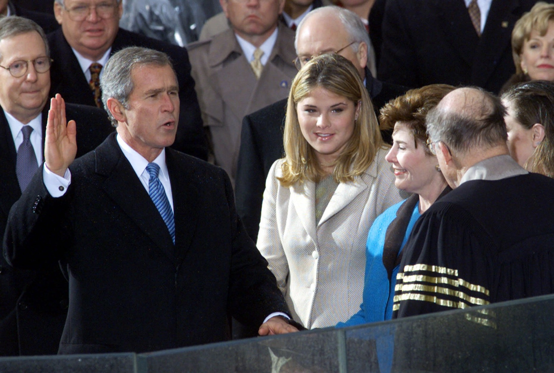 George W. Bush takes the oath of office from Chief Justice William Rehnquist to become the 43rd president Saturday, Jan. 20, 2001, in Washington. Wife Laura Bush holds the Bible and daughter Jenna watches. (AP Photo/Doug Mills)