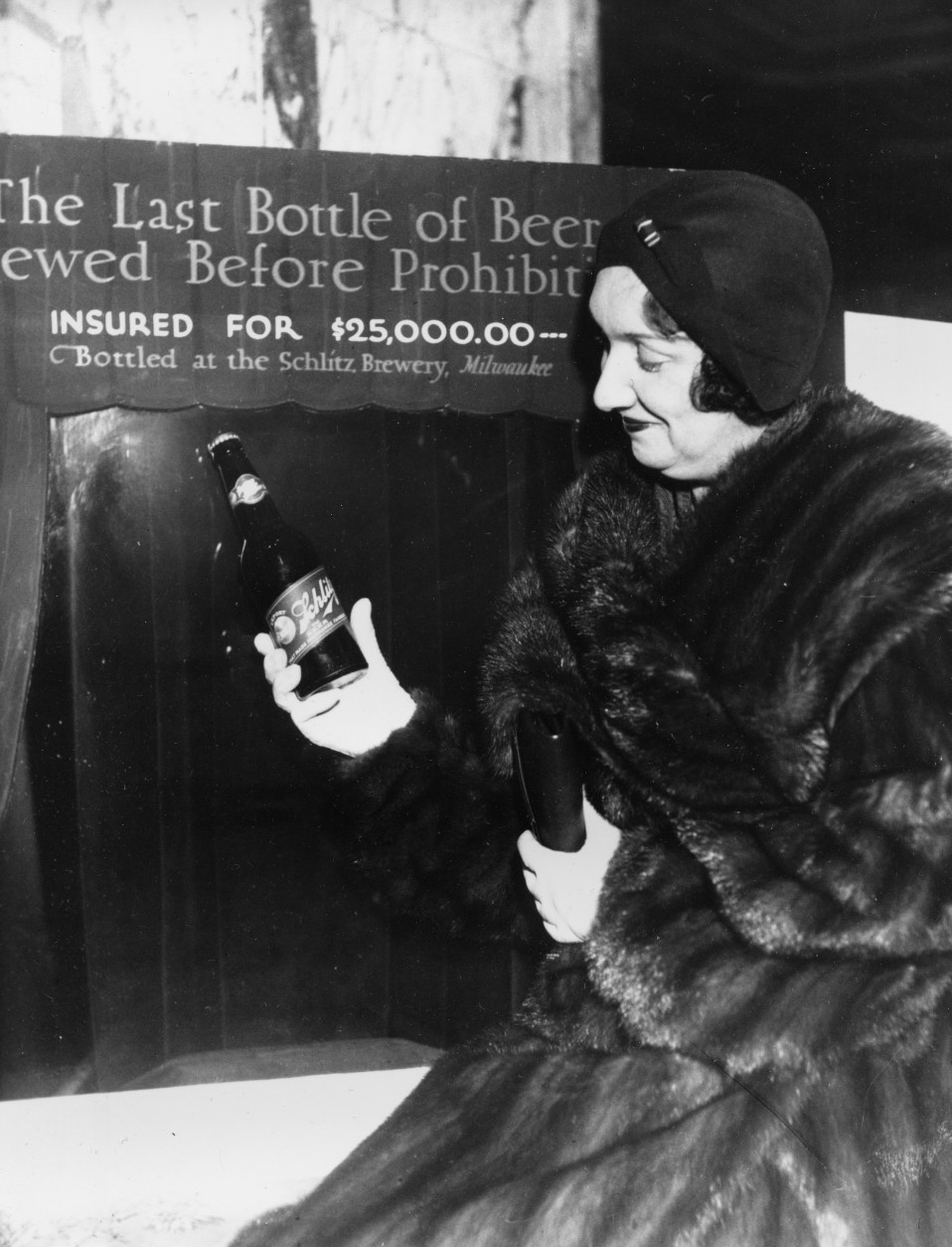 Rae Samuels holds the last bottle of beer that was distilled before prohibition went into effect in Chicago, Ill., Dec. 29, 1930.  The bottle of Schlitz has been insured for $25,000.  (AP Photo)