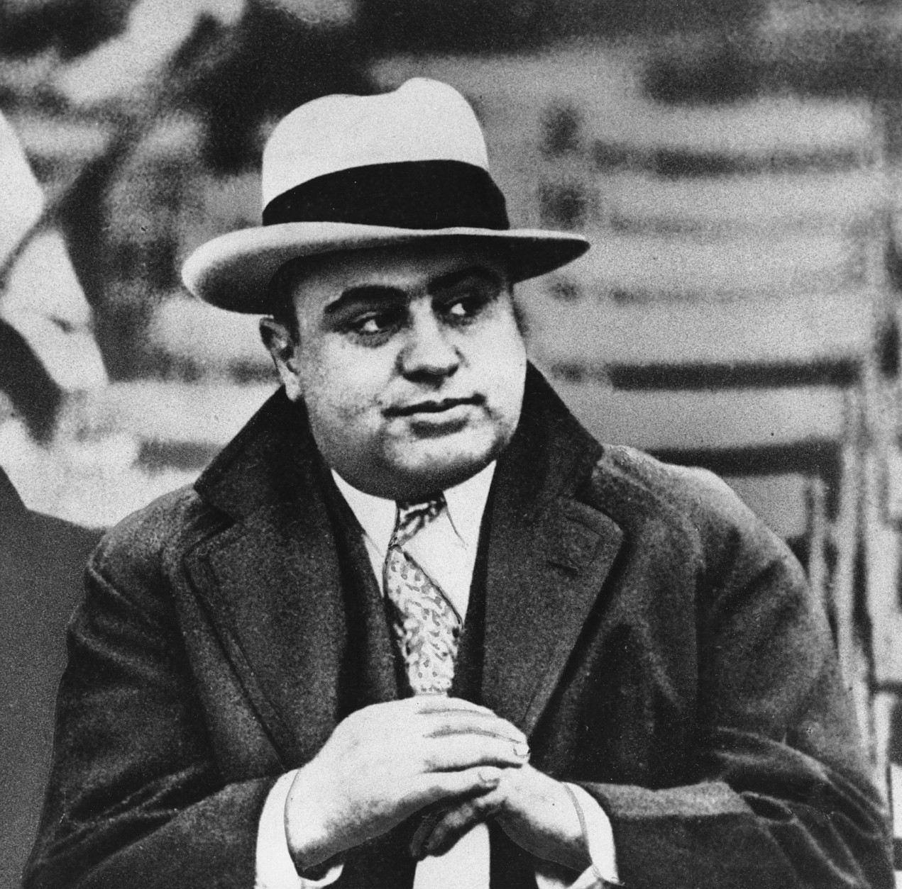 Al Capone is photographed at a football game in Chicago on Jan. 19, 1931.  Everywhere he went, people recognized him.  Capone always wore a loud tie, a bent brim fedora hat and camel's hair polo coat and always had an entourage of bodyguards.  (AP Photo)