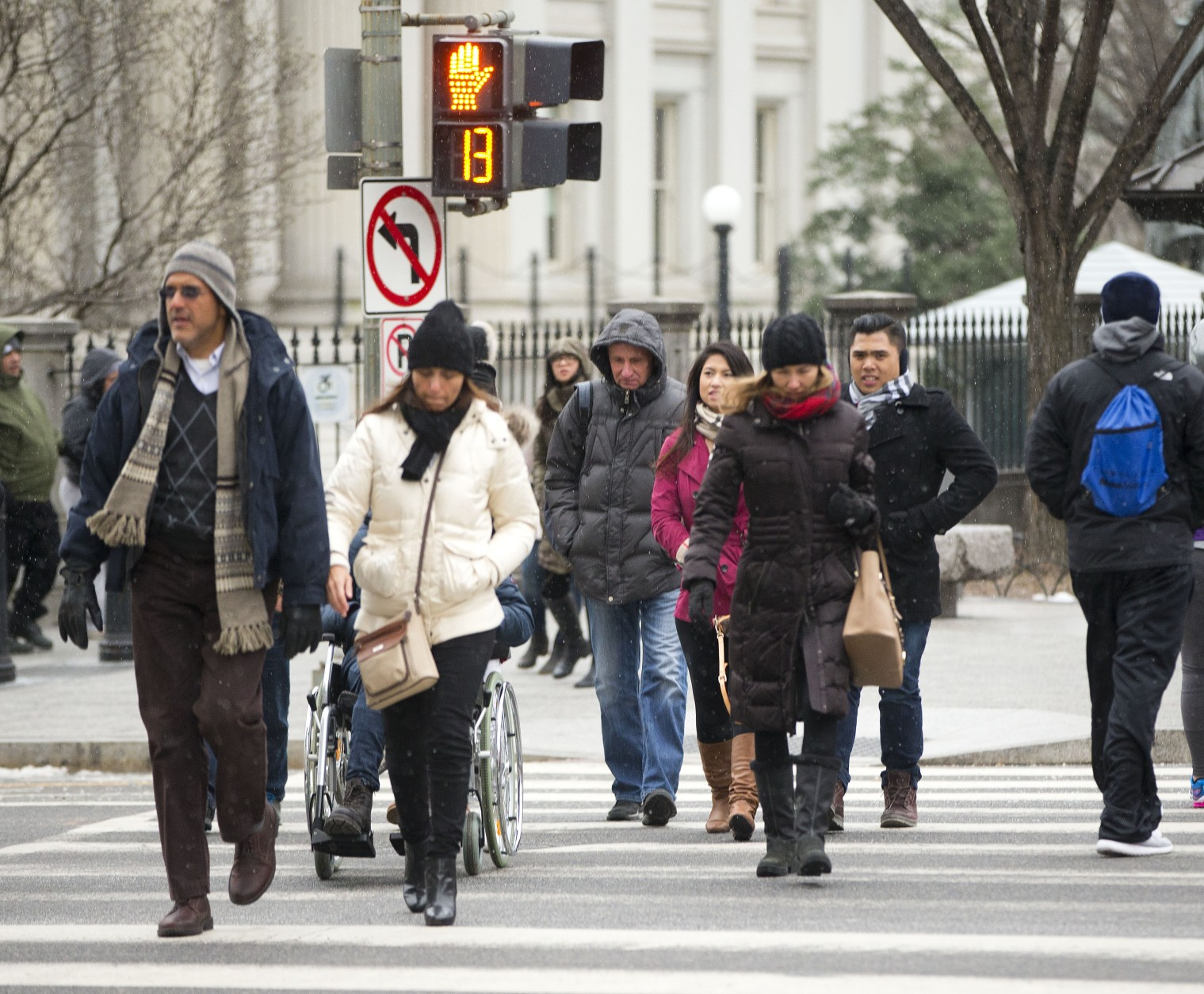 Pedestrians cross 15th Street in downtown Washington near the White House, Friday, Jan. 22, 2016, as the Nation's Capital hunkers down in preparation for a major snowstorm expected to begin later today. Food and supplies vanished from store shelves, five states and the District of Columbia declared states of emergency ahead of the slow-moving system. (AP Photo/Pablo Martinez Monsivais)