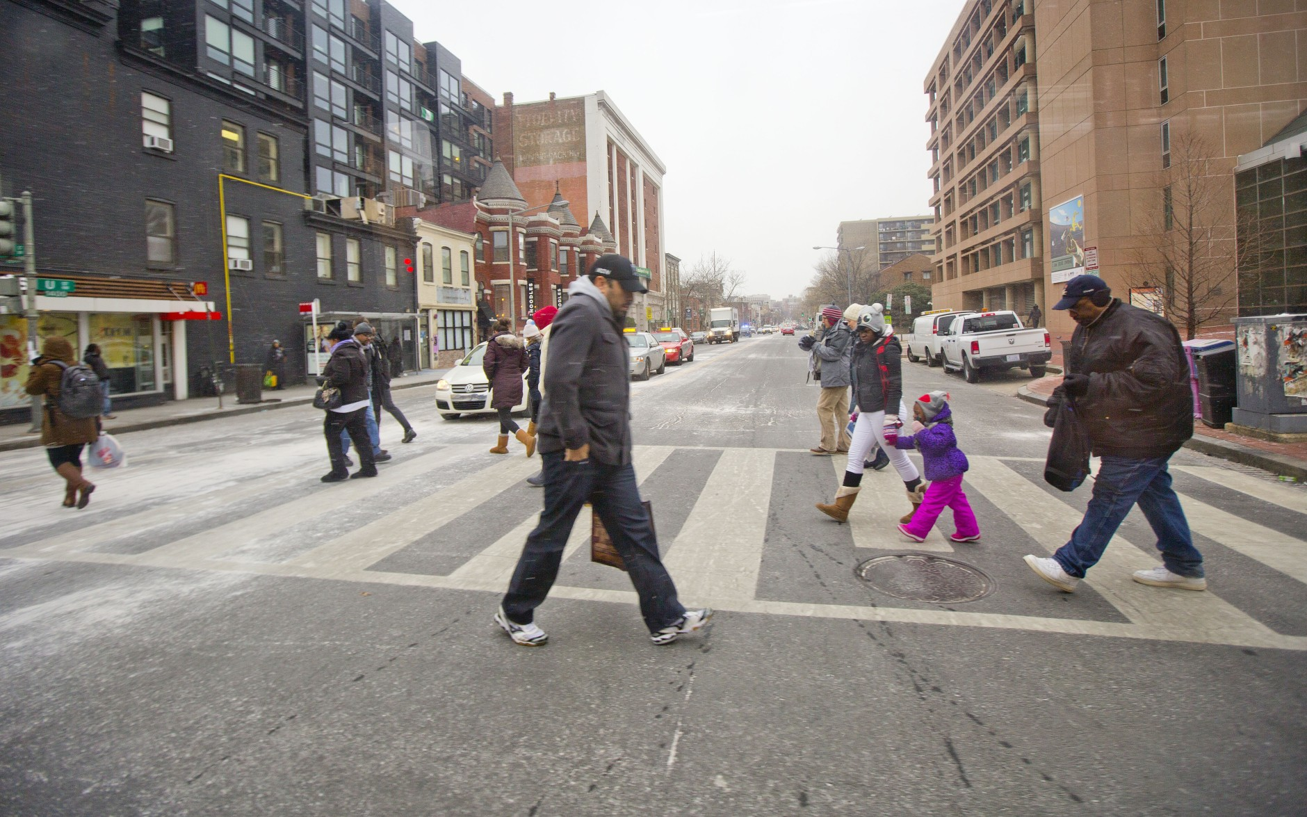Pedestrians cross an intersection of U street and 14th Street NW in Washington, Friday, Jan. 22, 2016, as the Nation's Capital hunkers down in preparation for a major snowstorm expected to begin later today. Food and supplies vanished from store shelves, five states and the District of Columbia declared states of emergency ahead of the slow-moving system. (AP Photo/Pablo Martinez Monsivais)