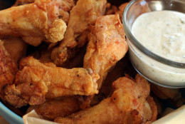 This Nov. 16, 2015 photo shows hands off party wings with cilantro sour cream dip and honey sriracha in Concord, N.H. (AP Photo/Matthew Mead)