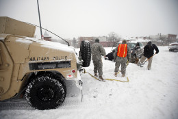 Soldiers with the 275th Military Police company, and a Washington Firefighter, in a Humvee, assist a stranded motorist in the snow on I-395, Saturday, Jan. 23, 2016 in Washington. (AP Photo/Alex Brandon)
