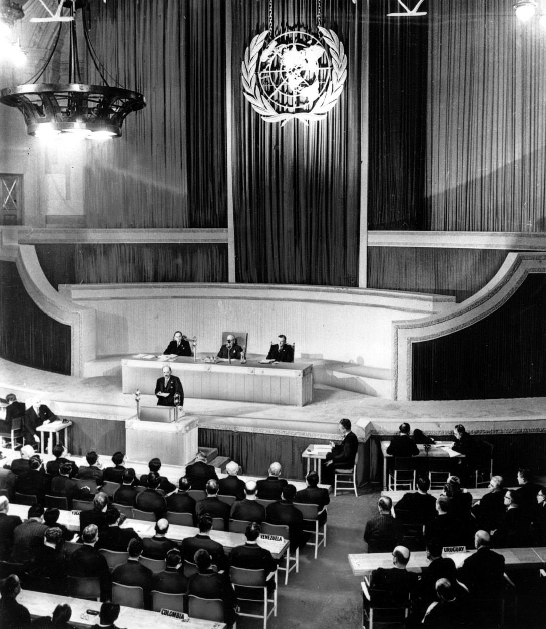 This is a general view of the first session of the United Nations Organization's General Assembly at Central Hall on Parliament Square in London, England, on January 10, 1946.  In his opening session address British Prime Minister Clement R. Attlee, on speaker's platform, warned that another war would destroy mankind. In the background is the U.N. emblem, the world surrounded by olive wreaths.  (AP Photo)
