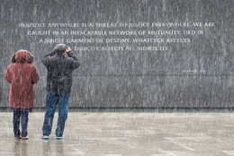 Visitors at the Martin Luther King, Jr. Memorial in Washington stop to photograph the quotes etched into the memorial's back wall while it snows on Sunday, Jan. 17, 2016.  (AP Photo/J. David Ake)