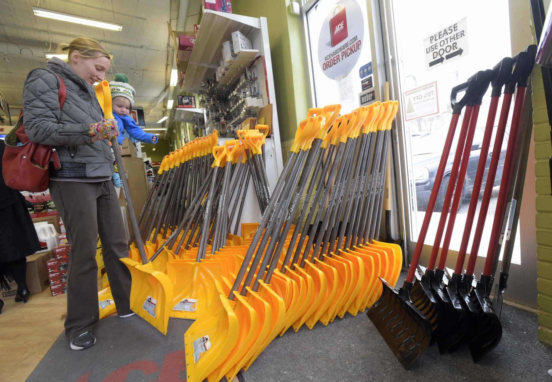 Bethany Gallagher, of Baltimore, shops for a snow shovel with her 18-month-old son, Jack, at the Waverly Ace Hardware store, in Baltimore, Friday, Jan. 22, 2016. The northern mid-Atlantic region, including Baltimore, Washington and Philadelphia, is preparing for a weekend snowstorm that is now forecast to reach blizzard conditions. (AP Photo/Steve Ruark)