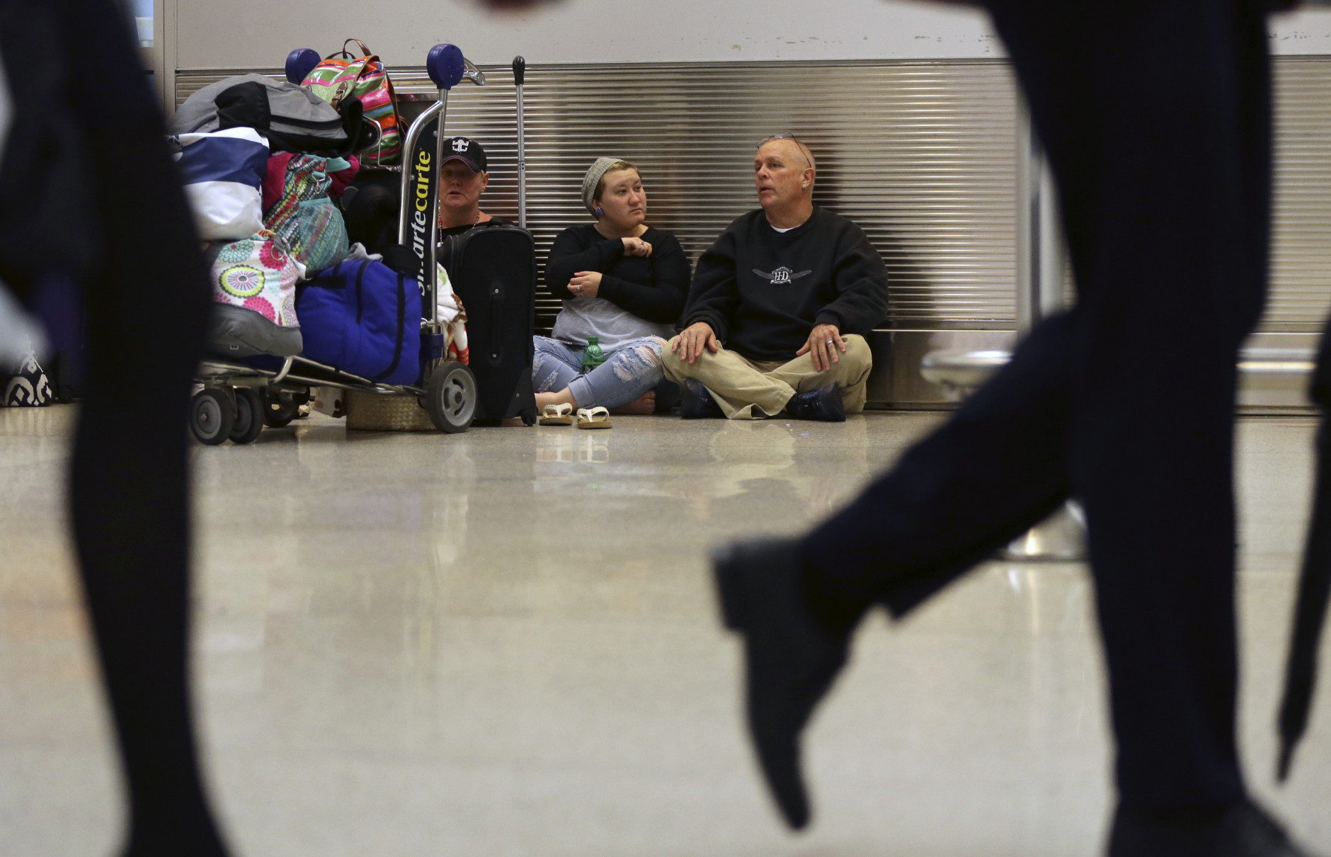Tracey Shelton, left, Paige Willey, center, and Warren Willey, right, of Crisfield, Md., wait to reschedule a flight at Miami International Airport, as their flight to Baltimore was canceled, Friday, Jan. 22, 2016, in Miami. Airlines have canceled more than 2,700 flights Friday to, from or within the U.S., as a blizzard swings up the East Coast, according to flight tracking service FlightAware. (AP Photo/Lynne Sladky)