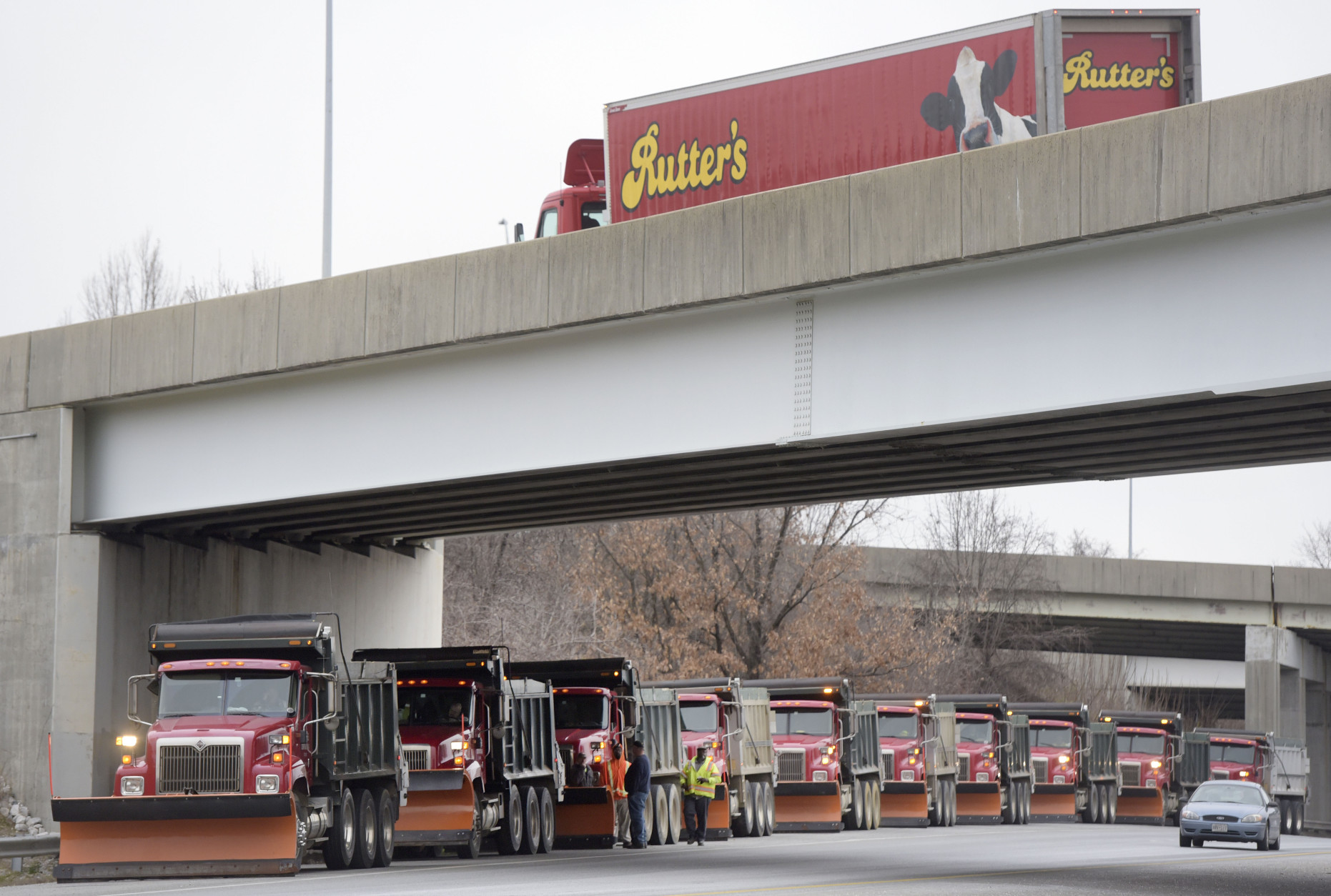 Snowplow operators gather on Interstate 97 as a dairy truck, top, moves along an overpass, Friday, Jan. 22, 2016, in Glen Burnie, Md., near Baltimore. (AP Photo/Steve Ruark)