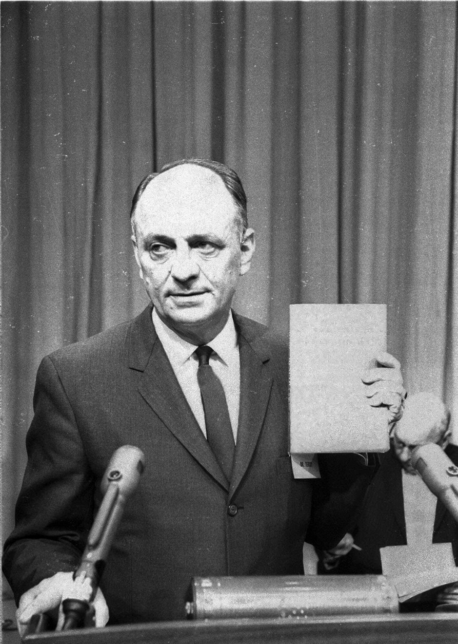 U.S. Surgeon General Luther Terry holds a copy of the 387 page report of the Advisory Committe to the Surgeon General of the Public Health Service on the relationsship of smoking to health Jan. 11, 1964.  He spoke at a Washington news conference at which the study was released.  It termed smoking a health hazard calling for corrective action. (AP Photo/hwg)