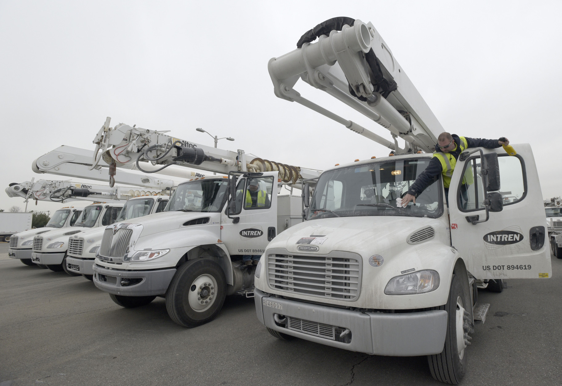 Utility worker Nick Bons, right, of Dorand, Ill., cleans his truck's windshield at a staging center for out-of-state utility workers in Hanover, Md., near Baltimore, Friday, Jan. 22, 2016. The northern mid-Atlantic region, including Baltimore, Washington and Philadelphia, is preparing for a weekend snowstorm that is now forecast to reach blizzard conditions. (AP Photo/Steve Ruark)