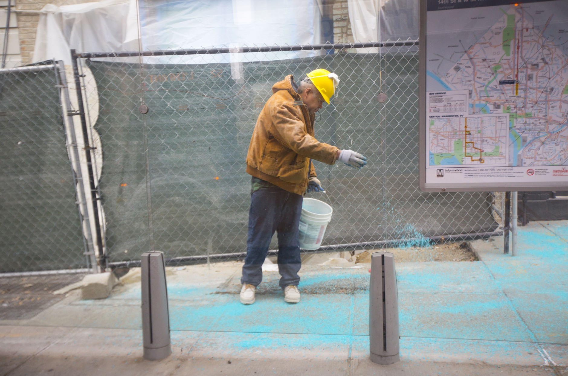 A construction worker treats the sidewalk near a bus stop on 14th Street NW in the Columbia Heights neighborhood of Washington, Friday, Jan. 22, 2016, as the nation's capital hunkers down in preparation for a major snowstorm. Food and supplies vanished from store shelves, five states and the District of Columbia declared states of emergency ahead of the slow-moving system. (AP Photo/Pablo Martinez Monsivais)