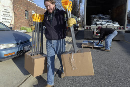 Vincent Ayd, left, owner of Ayd Hardware in Towson, Md., and truck driver Mike Jock, of Newark, Del., unload snow shovels and ice-melt in Towson, Thursday, Jan. 21, 2016. The northern mid-Atlantic region, including Baltimore, Washington and Philadelphia, is preparing for a weekend snowstorm that is now forecast to reach blizzard conditions. (AP Photo/Steve Ruark)