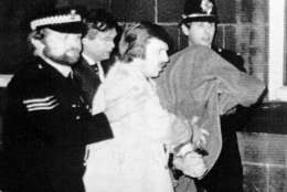 Peter William Sutcliffe, 35, is led from Dewsbury Magistrates Court in Dewsbury on Monday, Jan. 5, 1981 under a blanket, by police officers at right two men look from a window. Sutcliffe was remanded in custody for eight days charged with the murder, November 17, 1980 of 20-year-old student Jacqueline Hill, who has been described as the 13th victim of the Yorkshire Ripper. (AP Photo/Pyne)