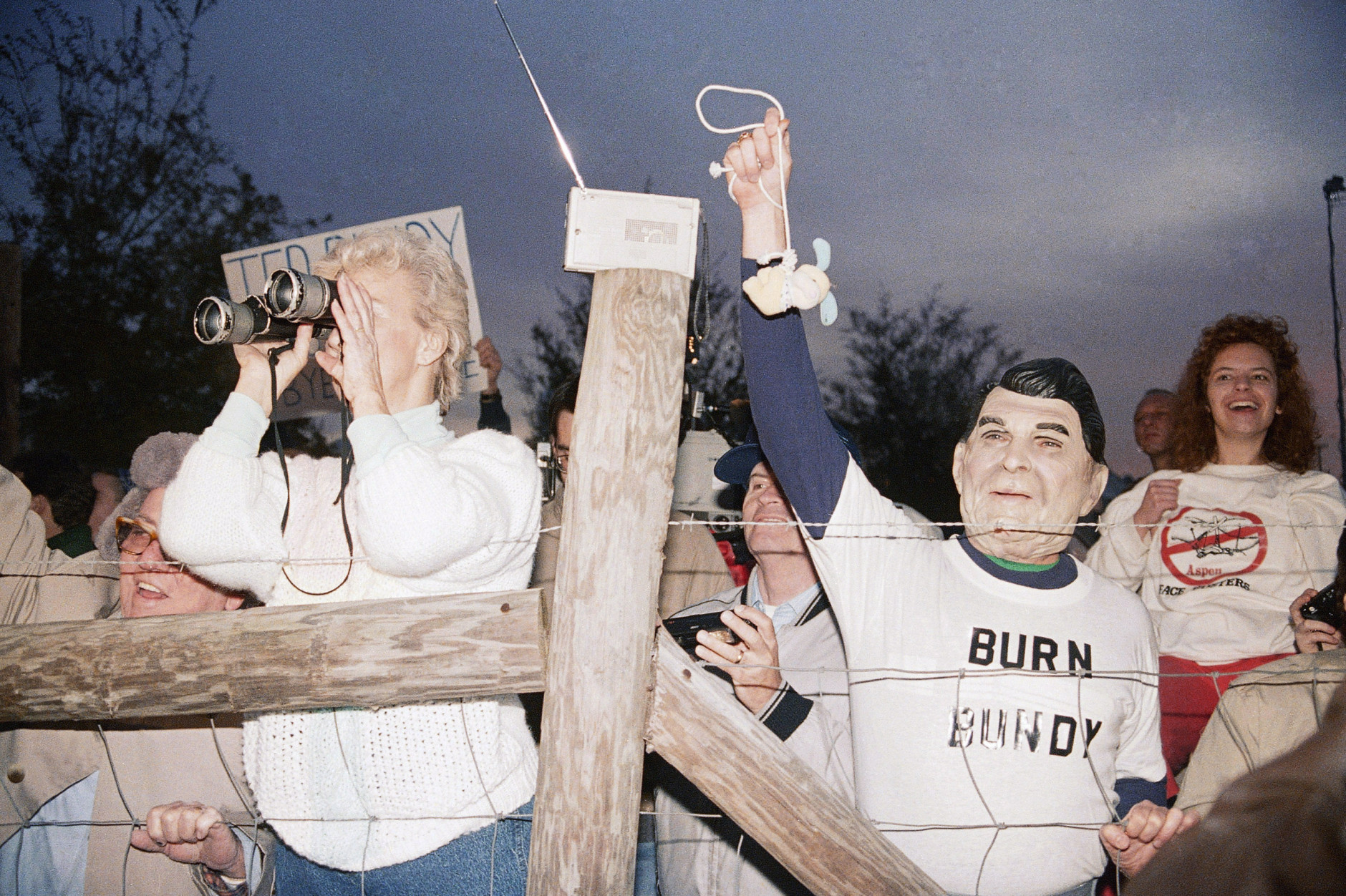 A toy bunny is hung in effigy by Jerry Jackson of Atlanta Ga., wearing a Ronald Reagan mask, and the pro-death penalty crowd rejoices after the Theodore Bundy execution, Jan. 25, 1989 at sunrise in Starke, Fla. (AP Photo/Mark Foley)