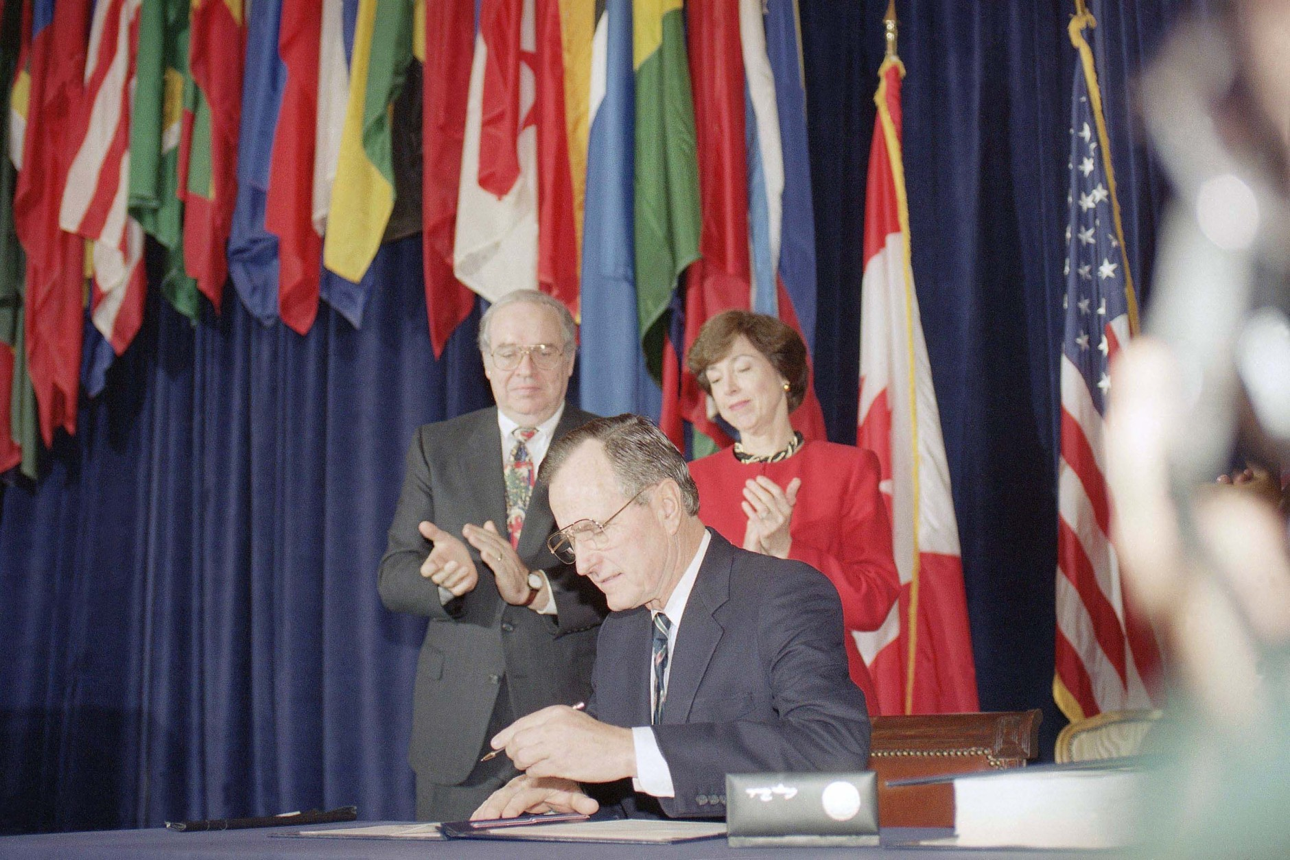Pres. George H. W. Bush, center, signs the North American Free Trade Agreement during a ceremony at the Organization of American States headquarters, Thursday, Dec. 17, 1992, Washington, D.C. Canadian Amb. Derek Burney and U.S. Trade Representative Carla Hills applaud during the signing. The president predicted an explosion of growth throughout North America as he signed the agreement. (AP Photo/Dennis Cook)