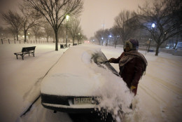 Ndimyake Mwakalyelye cleans off her car after getting off work, as the snow continues to fall, Friday, Jan. 22, 2016 in Washington. (AP Photo/Alex Brandon)