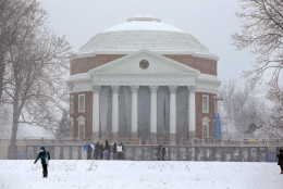 Students walk on the lawn in front of the Rotunda at the University of Virginia as snow falls, Friday, Jan. 22, 2016, in Charlottesville, Va.  (Andrew Shurtleff/The Daily Progress via AP) MANDATORY CREDIT