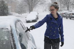 Taylor Mushtare scrapes ice and snow from her car in Old Southwest Roanoke, Va., Friday morning, Jan. 22, 2016.  A blizzard menacing the Eastern United States started dumping snow in Virginia, Tennessee and other parts of the South on Friday as millions of people in the storm's path prepared for icy roads, possible power outages and other treacherous conditions. (Heather Rousseau/The Roanoke Times via AP) LOCAL TELEVISION OUT; SALEM TIMES REGISTER OUT; FINCASTLE HERALD OUT;  CHRISTIANBURG NEWS MESSENGER OUT; RADFORD NEWS JOURNAL OUT; ROANOKE STAR SENTINEL OUT; MANDATORY CREDIT