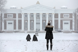 Students walk on the lawn in front of Old Cabell Hall at the University of Virginia as snow falls, Friday, Jan. 22, 2016, in Charlottesville, Va.  (Andrew Shurtleff/The Daily Progress via AP) MANDATORY CREDIT
