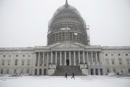 Two runners jog as the snow falls on Capitol Hill, Friday, Jan. 22, 2016, in Washington. One in seven Americans will get at least half a foot of snow outside their homes when this weekend's big storm has finished delivering blizzards, gale-force winds, whiteout conditions and flooding to much of the eastern United States. (AP Photo/Alex Brandon)