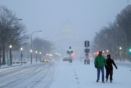 Madison Riley, left, and Katie Lantuh walk down the middle of Pennsylvania Avenue with the U.S. Capitol behind them, as the snow falls, Friday, Jan. 22, 2016 in Washington. One in seven Americans will get at least half a foot of snow outside their homes when this weekend's big storm has finished delivering blizzards, gale-force winds, whiteout conditions and flooding to much of the eastern United States. (AP Photo/Alex Brandon)