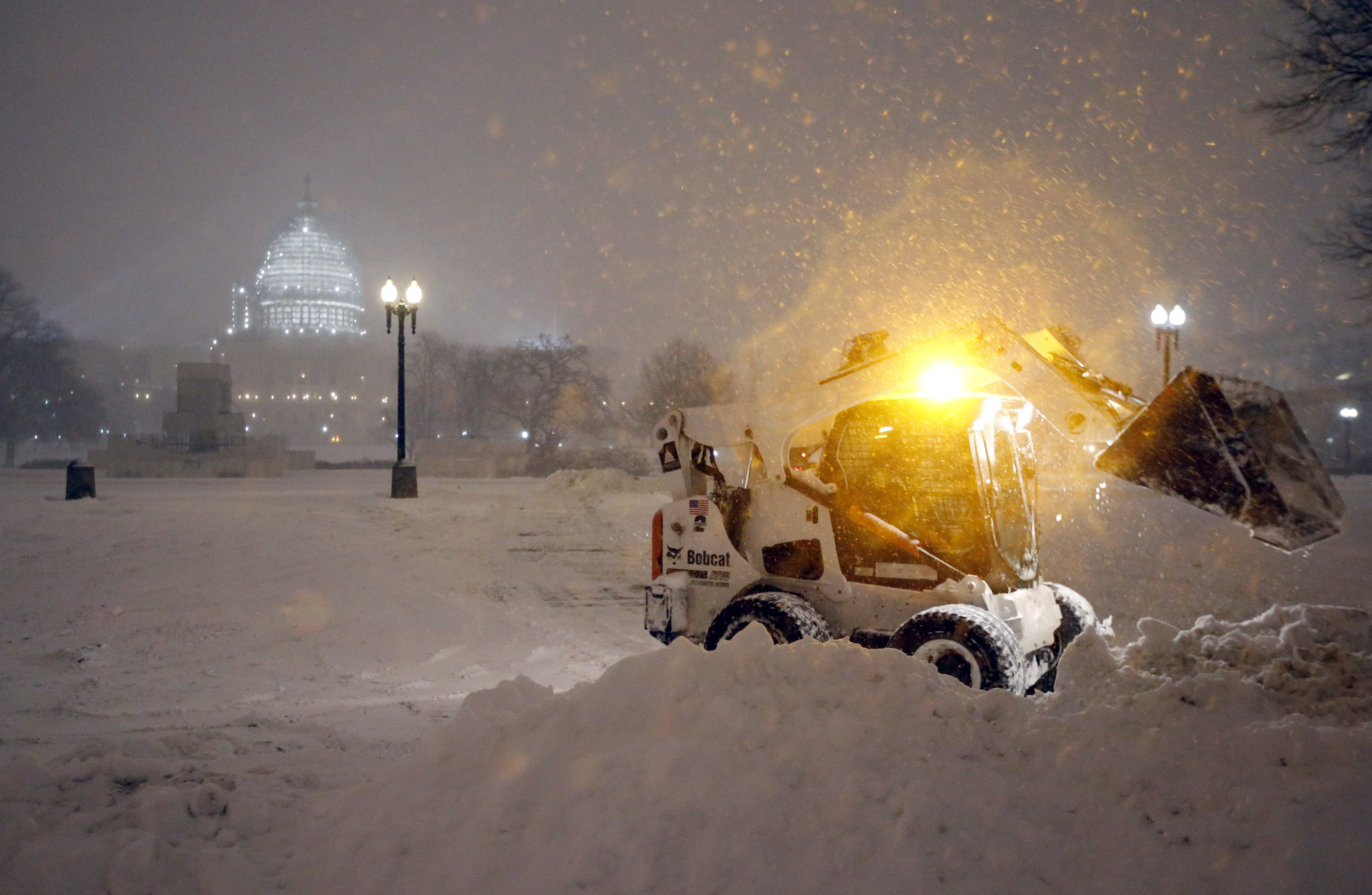 A bobcat piles up snow in front of the U.S. Capitol, as the snow continues to fall, Friday, Jan. 22, 2016, in Washington. (AP Photo/Alex Brandon)
