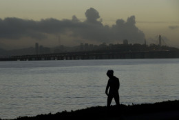 A woman walks along a path as clouds hang over the San Francisco-Oakland Bay Bridge in Emeryville, Calif., Tuesday, Jan. 5, 2016. El Nino storms lined up in the Pacific, promising to drench parts of the West for more than two weeks and increasing fears of mudslides and flash floods in regions stripped bare by wildfires. (AP Photo/Jeff Chiu)