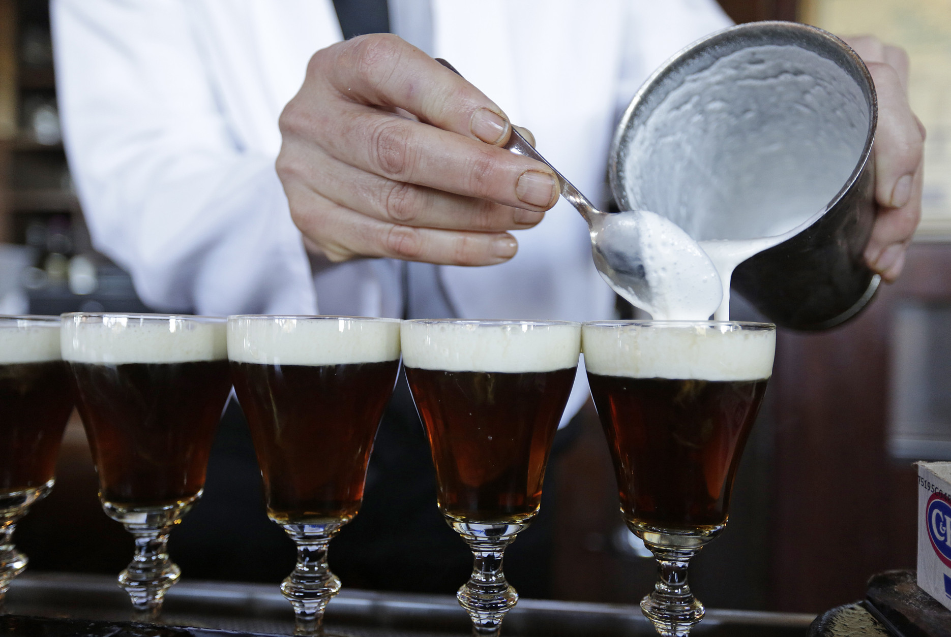 In this photo taken Tuesday, Dec. 15, 2015, bartender Paul Nolan makes Irish Coffee drinks at the Buena Vista Cafe in San Francisco. The drink has been made at the popular bar since 1952 and up to 2,000 are served a day. (AP Photo/Eric Risberg)