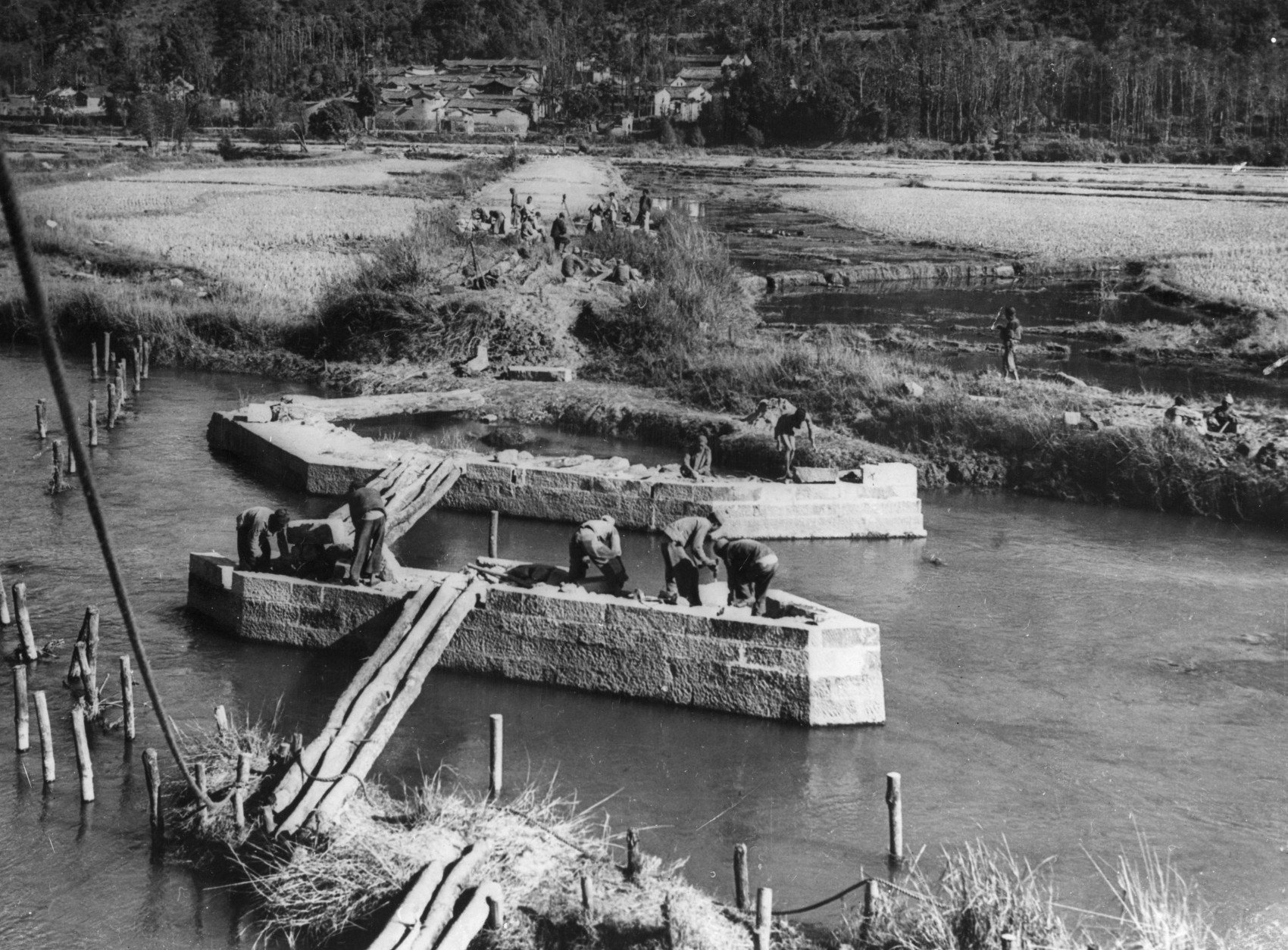 2nd July 1945:  Stonemasons working on the piers of a bridge across the Tisung River in Yunnan Province, China, in order to extend the length of the Stilwell Road. The road is being used by the Allied forces as an overland route to bring supplies to the Chinese Army after routing the Japanese.  (Photo by Keystone/Getty Images)