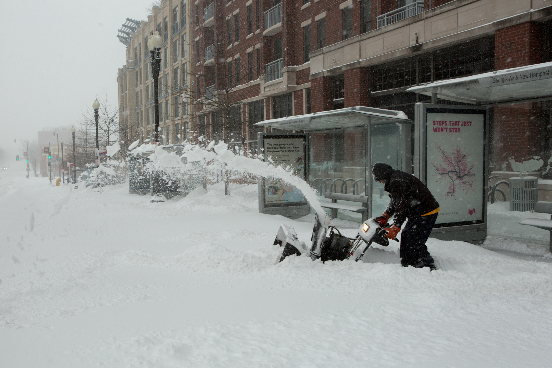 A man uses a snow blower to clear a sidewalk in front of the shuttered Georgia Ave.-Petworth metro station on January 23, 2016 in Washington, DC. Over a foot of snow has already fallen in the city in the past 24 hours, in what experts say could be a record-breaking storm.  (Photo by Allison Shelley/Getty Images)