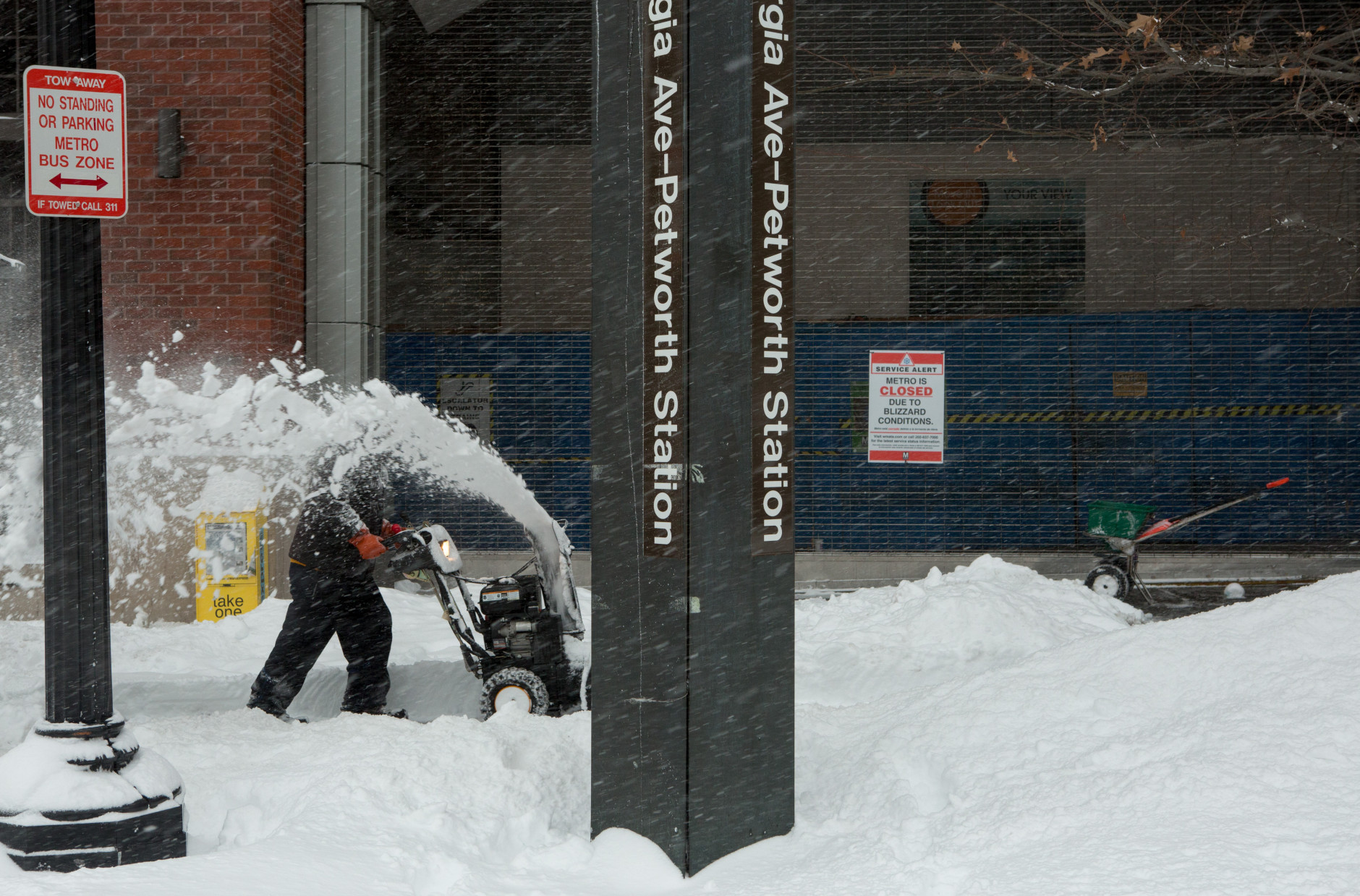 WASHINGTON, DC - JANUARY 23:  A man uses a snow blower to clear a sidewalk in front of the shuttered Georgia Ave.-Petworth metro station on January 23, 2016 in Washington, DC. Over a foot of snow has already fallen in the city in the past 24 hours, in what experts say could be a record-breaking storm.  (Photo by Allison Shelley/Getty Images)