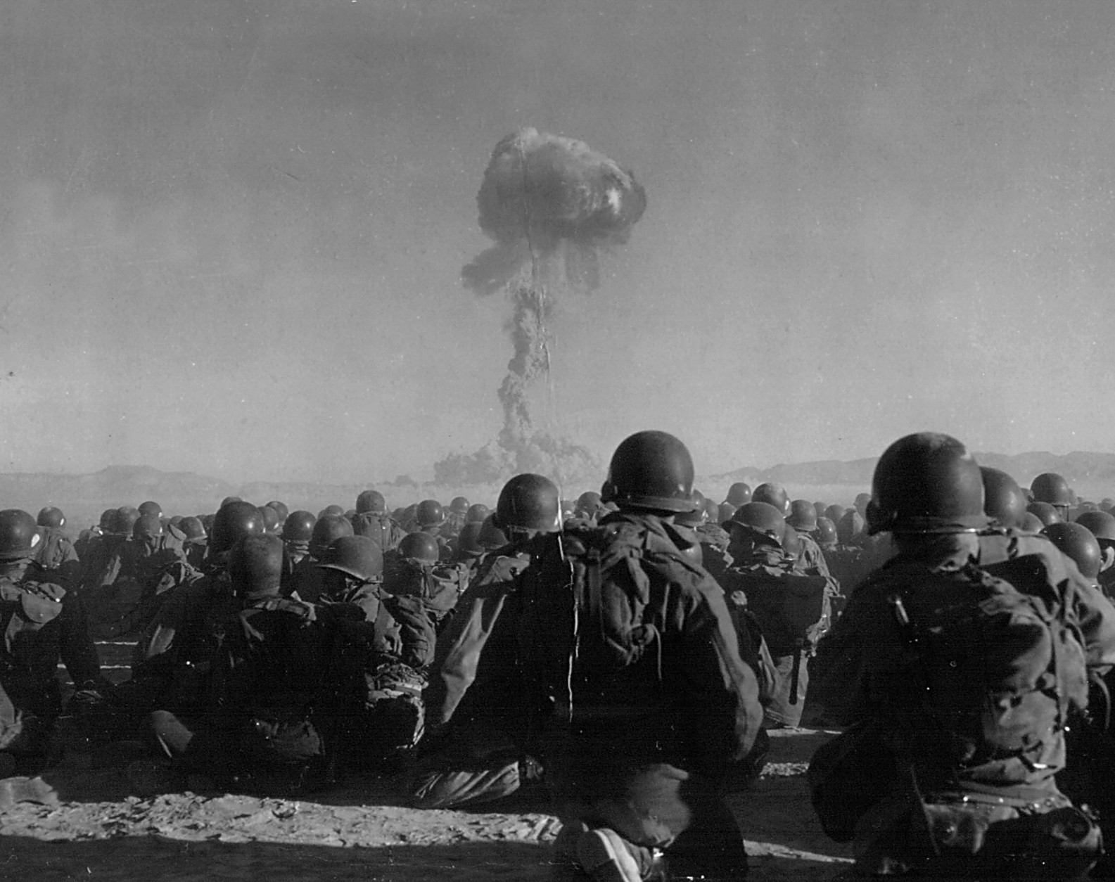 379631 13: Troops of the U.S. Army 11th Airborne Division watch a plume of radioactive smoke rise November 1, 1951 after a blast at Yucca Flats, Nevada . (Photo by National Archive/Newsmakers)
