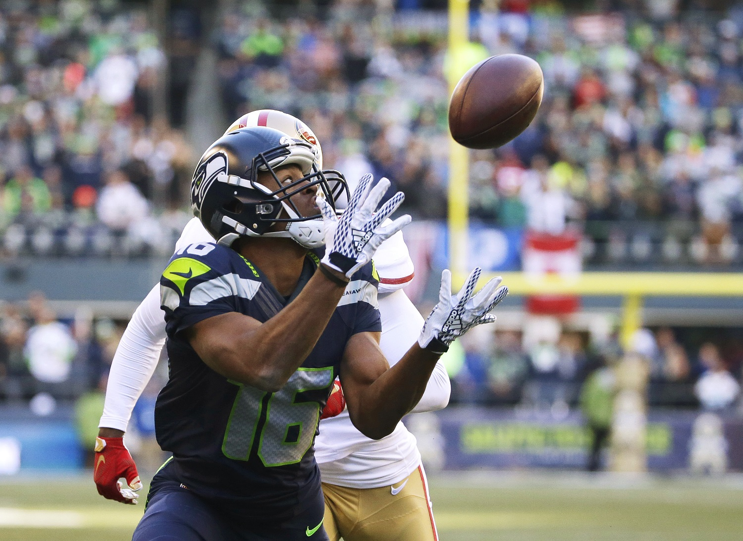 Seattle Seahawks wide receiver Tyler Lockett (16) catches a pass for a touchdown in front of San Francisco 49ers strong safety Jimmie Ward during the first half of an NFL football game, Sunday, Nov. 22, 2015, in Seattle. (AP Photo/Elaine Thompson)