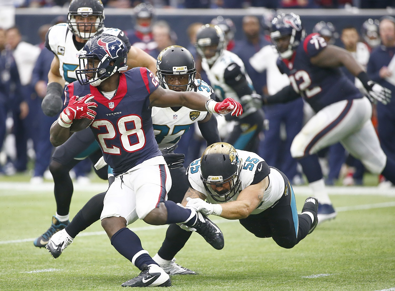 HOUSTON, TX - JANUARY 03: Alfred Blue #28 of the Houston Texans breaks the tackle of Dan Skuta #55 of the Jacksonville Jaguars on January 3, 2016 at NRG Stadium in Houston, Texas. (Photo by Scott Halleran/Getty Images)