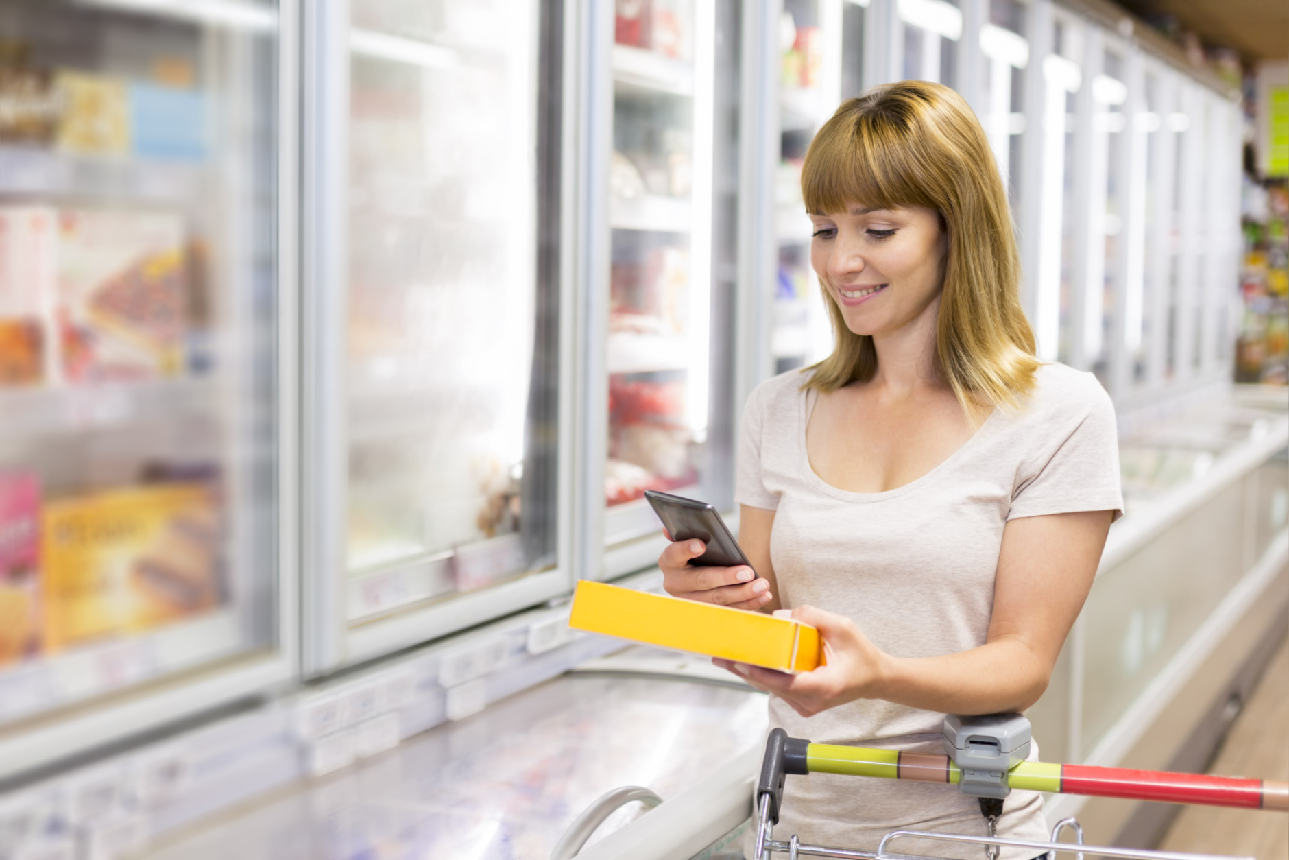 Cheerful young woman texting on mobile phone in supermarket.