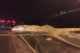 A mound of snow in an intersection and shiny black ice on the road combine to create a difficult and unsafe maneuver onto Waples Mill Road. (WTOP/Dennis Foley)