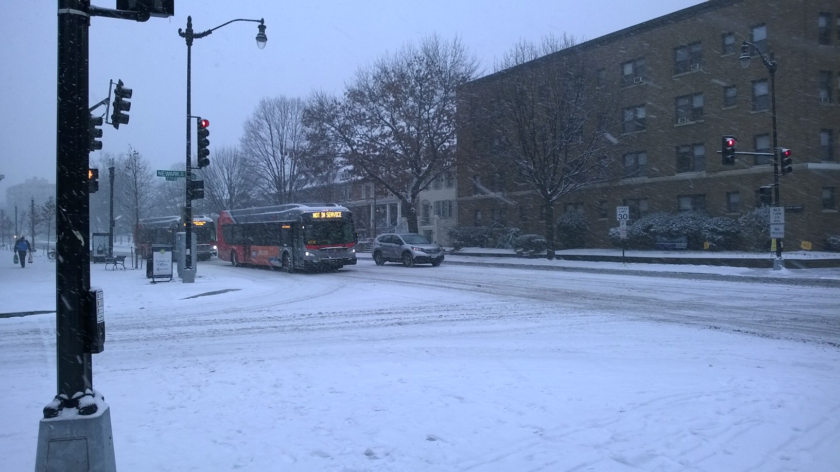 A bus traverses the snow on Wisconsin Ave. in Washington, D.C. on Friday, Jan. 22, 2016. Due to a massive snow storm, public transit will be shut down in the District Friday evening and through the weekend. (WTOP Staff)