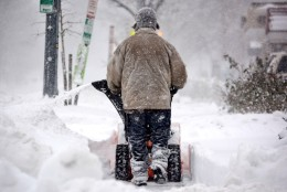 A man clears a sidewalk with a snowblower in January 2016 in D.C. (WTOP/Dave Dildine)