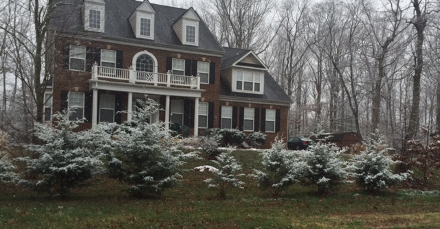 Snow flurries fall on a house in Waldorf, Maryland on Sunday, Jan. 17, 2016.