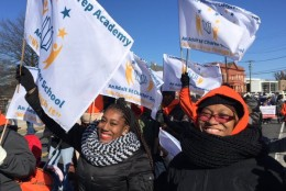 Dereka Coleman and Simona Coleman wave flags for Community College Preparatory Academy at the MLK Peace Walk in D.C. (WTOP/Kristi King)